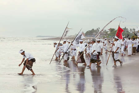 BALI, INDONESIA - MARCH 28: Balinese men do the ablution in the ocean after a procession from the center of the island to the ocean coast for the annual ceremony of purification Melasti on the Berawa beach, Bali on March 28, 2014
