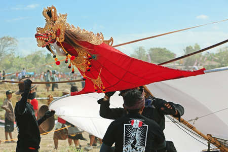 adult indonesia: BALI, INDONESIA - JULY 15: Unidentified young men preparing to launch a huge kite decorated with a dragon head in adornments and crown, wings and long striped tail during the annual festival of traditional Balinese kites on the beach Galak in Bali island