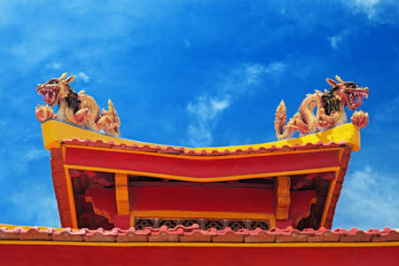 buddhist temple roof: Two colorful dragon on the roof of a Buddhist temple against the blue sky