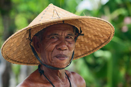 bali province: BALI, INDONESIA - MARCH 20: Portrait of an unidentified old Balinese farmer with a wrinkled face in traditional straw wide-brimmed hat during harvesting rice crop in the rice terraces field in Bali island on 20 March, 2015