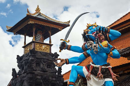 cut off head: Blue coloured traditional demon ogoh-ogoh holding a severed head and decorated with skulls before the annual parade of horrible monsters - pengrupukan, which is held in the evening of Nyepi - Balinese New Year before the day of silence Stock Photo