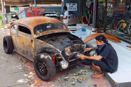 BALI, INDONESIA - MARCH 20: Young Balinese man cleans a body of an old volkswagen beetle during the making and vintage custom hotrod car in the auto and moto repair shop in Bali island on 20 March, 2015