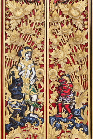 door leaf: Traditional carved wood door painted in gold and red colors in a Balinese temple decorated with floral ornaments and scenes from Hindu mythology with people figures,  Bali art backgrounds