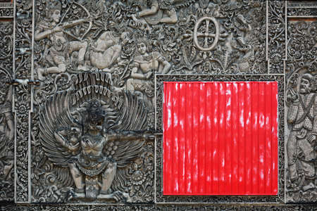 Ancient Balinese stone carving on the wall partially closed by red square shield with traditional characters of the Hindu religion and a symbol of Indonesia - mythical bird Garuda, Asian backgrounds photo