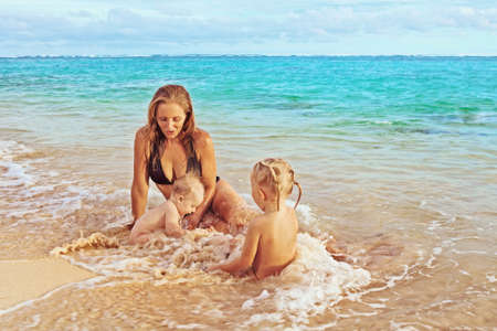 playing in the sea: Beautiful smiling young mother with her two little cute children - boy and girl playing joyfully in sea surf on a sand beach, joy of maternity and a healthy happy family on vacation on tropical island