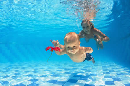 family swimming: In the pool young mother teaches to swim 10 month old baby - dive with cheerful boy deep into the water for a beautiful red flower, healthy lifestyle and children swimming lessons with an instructor