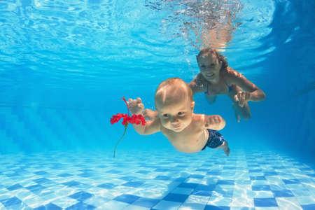 Nella piscina giovane madre insegna a nuotare bambino 10 mesi - immersione con ragazzo allegro in profondità in acqua per un bel fiore rosso, stile di vita sano e bambini lezioni di nuoto con un istruttore