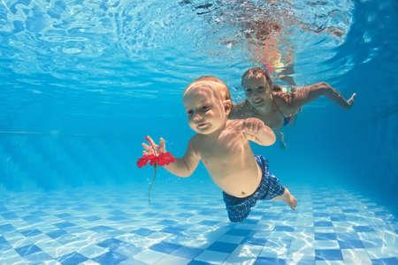 Ung mor lär att simma 10 månader gammal baby - Dyk med glada barn djupt i vattnet för röd blomma, hälsosam livsstil och barn vattens simlektioner med en instruktör i poolen