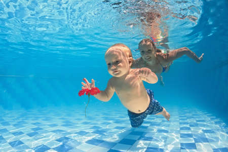 Young mother teaches to swim 10 month old baby - dive with cheerful child deep into the water for red flower, healthy lifestyle and children underwater swimming lessons with an instructor in the pool