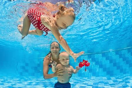 Ung mor l�r att simma 10 m�nader gammal baby - Dyk med glada barn djupt i det bl� vattnet, h�lsosam livsstil och barn vattens simlektioner med en instrukt�r i poolen Stockfoto