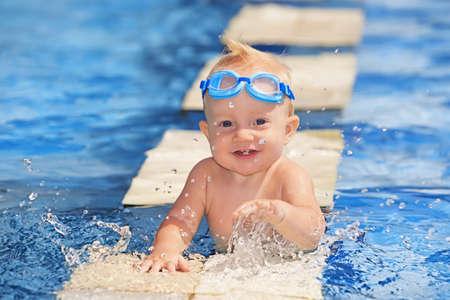 Glad leende älskling med första tänder och undervattensglasögon, leker med stänk i klart blått vatten i poolen innan simningstimer, hälsosam livsstil, sommaraktivitet och undervisning av barn att simma