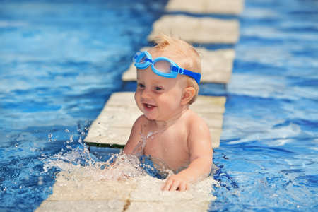 Happy smiling baby with underwater goggles is having fun playing with splashes in blue water in pool before swimming lessons. Lifestyle and summer children activity in vacation in tropical resort Stock Photo