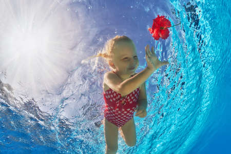 Happy little baby with smile and open eyes diving in the clear blue water for a bright red flower.Healthy lifestyle and children underwater swimming during summer vacation in the tropical resort pool Stockfoto