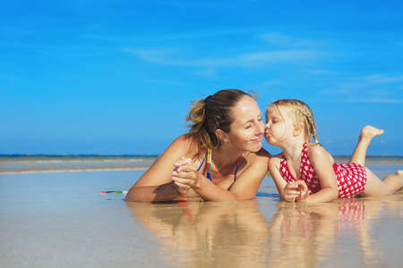beach kiss: Small child playing with fun and kissing happy young mother smiling with love to her daughter lying on wet sand sea beach. Family lifestyle and summer vacation with children on tropical island resort Stock Photo