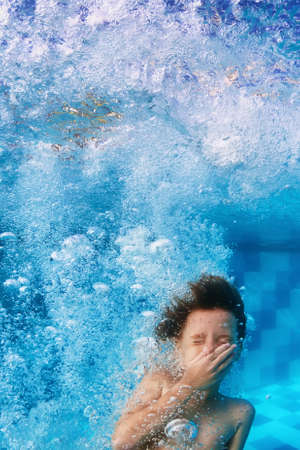 underwater: Amusing face portrait of smiling boy swimming and diving in blue pool with fun - jumping down underwater with splashes and foam. Family lifestyle and summer children water sports activity with parents Stock Photo