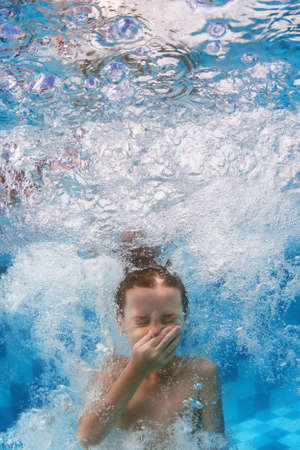 Funny face portrait of boy swimming and diving in blue pool with fun - jumping deep down underwater with splashes and foam. Family lifestyle and summer children water sports activity with parents