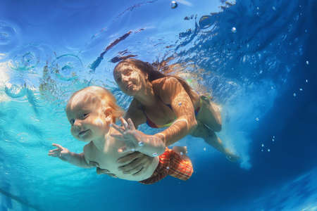 In blue pool young mother swimming with happy baby son - dive underwater with cheerful boy. Healthy family lifestyle and children water sports activity with parents during summer vacation with child Banque d'images