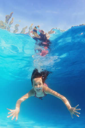 Underwater portrait of happy girl with smiling face swimming in blue pool. Healthy family lifestyle, physical development and children water sports activity with parents on summer vacation with child.