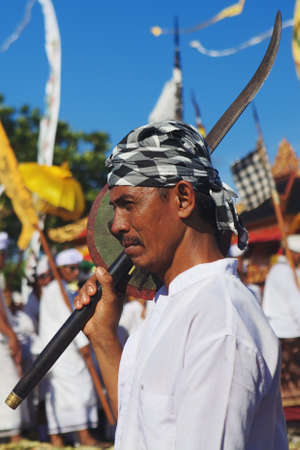 buckler: BALI INDONESIA  MARCH 18: Face portrait of an unidentified hindu man dressed in rite clothing with a traditional Balinese ceremonial sword before ritual fighting dance during annual purification ceremony Melasti. Culture and religions of Indonesian people