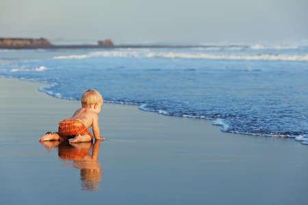 Op de zonsondergang strand grappige baby kruipen op zwart natte zand naar zee surfen om te zwemmen in de golven. Familie lifestyle en water activiteit tijdens de zomervakantie met kind op het tropische eiland Bali Stockfoto
