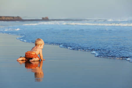 Sur la plage coucher de soleil bébé drôle rampant sur le sable humide de la mer noire surf pour nager dans les vagues. Mode de vie de la famille et de l'activité de l'eau pendant les vacances d'été avec un enfant sur l'île tropicale de Bali