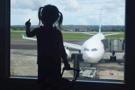 Silhouet van kleine baby meisje te wachten aan boord voor haar vlucht in de luchthaven transit hal en op zoek naar het vliegtuig parkeerplaats bij gate. Reizen door de lucht met een kind tijdens familie zomervakantie