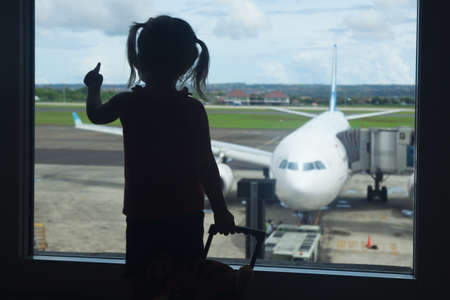 Silhouette of little baby girl waiting boarding to her flight in airport transit hall and looking at airplane parking near departure gate. Travelling by air with child during family summer vacation