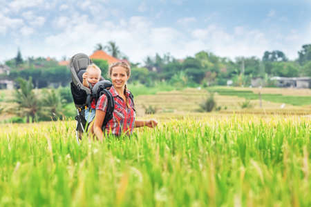 baby rice: Cheerful mother with baby boy in carrying backpack walking on green rice terraces. Travelling with child active and healthy lifestyle during family summer vacation with son on Asian tropical island