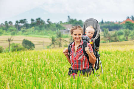 Happy mother with baby boy in carrying backpack trekking on green rice terraces. Travelling with child active and healthy lifestyle during family summer vacation with son on  tropical island Bali Stockfoto