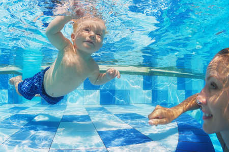 Portrait of child swimming with fun underwater in pool with diving cheerful mother. Healthy lifestyle active parenting and children water sports activity during summer family vacation with baby boy