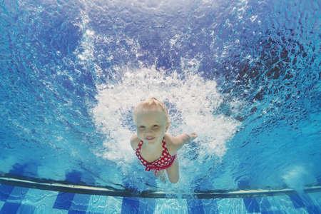 underwater: Baby girl swimming underwater and diving in pool with fun  jumping deep down with splashes Active lifestyle water sports activity and exercising with parents during summer family vacation with child Stock Photo