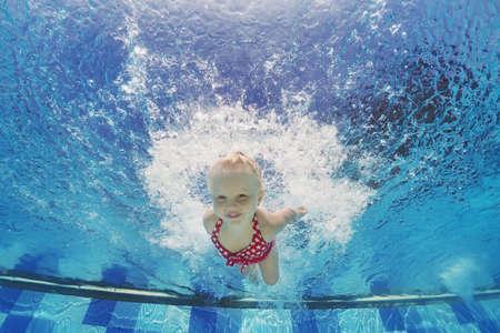 Baby meisje onderwater zwemmen en duiken in het zwembad met plezier springen diep met spatten Actieve leefstijl watersport activiteiten en het uitoefenen met de ouders in de zomer familie vakantie met kind