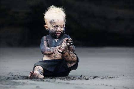座っていると遊んで楽しい黒砂海岸で海で泳ぐ前に汚れた顔で笑みを浮かべて子の面白い肖像画。赤ちゃんと一緒に夏休みに家族のアクティブなラ