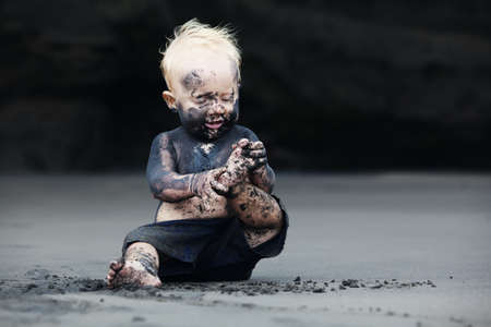 miry: Funny portrait of smiling child with dirty face sitting and playing with fun on black sand sea beach before swimming in ocean. Family active lifestyle and water leisure on summer vacation with baby