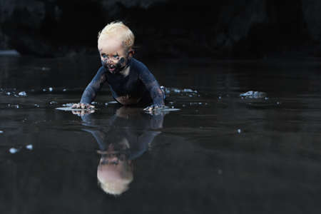 miry: On flat ocean beach dirty baby crawling with fun on wet black sand to sea surf for swimming in waves. Family lifestyle and water activity during summer vacation with child on tropical Bali island