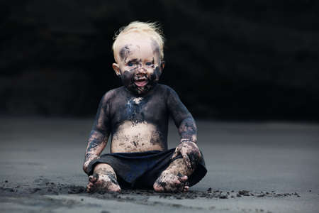 Funny portrait of smiling child with dirty face sitting and playing with fun on black sand sea beach before swimming in ocean. Family active lifestyle and water leisure on summer vacation with baby