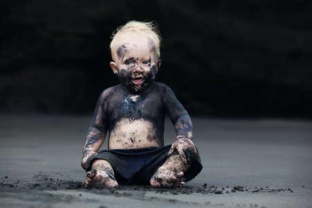 Grappig portret van glimlachend kind met vuile gezicht zitten en spelen met plezier op zwarte zee strand zand voor het zwemmen in de oceaan. Familie actieve levensstijl en water recreatie op zomervakantie met baby