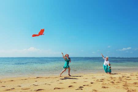 Carefree mamma har en rolig att köra med flygande röd drake på havet stranden flicka och mormor. Tre generationer av familjen glad föräldraskap och aktiv fritid under sommaren semester med barn
