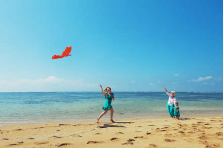 kites: Carefree mother having a fun running with flying red kite on sea beach to baby girl and grandmother. Three generations of family happy parenting and active leisure during summer vacation with child