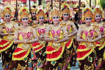 BALI INDONESIEN 13 JUNI: Oidentifierade människor med traditionell smink på ansikten och klädd i färgglada balinesiska dräkter på parad på Bali Art Festival 2015 i Denpasar Bali den 13 juni 2015