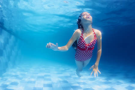 physical activity: Child swimming underwater lesson  girl diving with fun in blue pool. Healthy active family lifestyle physical development and children water sports activity with parents on summer vacation with kids Stock Photo