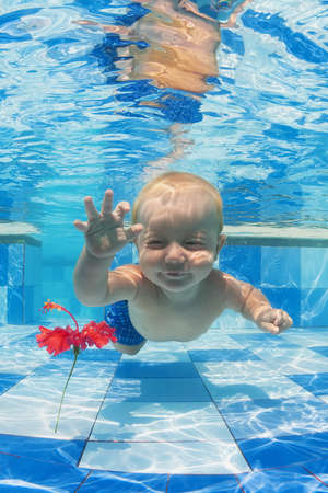 Smiling baby boy diving underwater with fun for red flower in blue pool Active lifestyle child swimming lesson with parents and water sports activity during family summer vacation in tropical resort