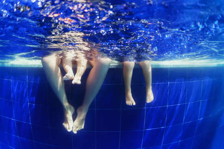 Ung mor simma under vattnet med roliga i poolen med pojke och liten flicka. Aktiv familj livsstil och barn vattensporter aktivitet med föräldrar under sommaren semester på tropisk resort