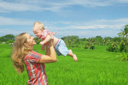 baby rice: Happy mother tossing up joyful baby boy on Balinese green rice terraces background. Outdoors healthy child activity active lifestyle on family summer vacation with son on Indonesian tropical island Stock Photo