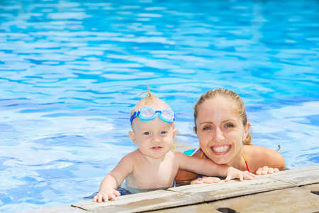 girl underwater: Joyful baby boy in underwater goggles swimming with fun with happy mother in outdoor pool. Active lifestyle, water sports activity and exercising with parents on summer family vacation with child