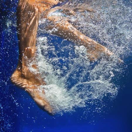 frescura: Natación de la muchacha con la diversión en la piscina de hidromasaje con agua azul limpia durante las vacaciones de verano de la familia en el centro turístico. Acción fotografía de pies femeninos mojados moviendo activamente bajo el agua con salpicaduras burbujas y ondulación