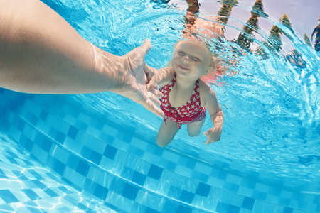Joyful baby girl diving underwater with fun and holding parents hand for assistance in swimming pool. Healthy active family lifestyle, children water sport activity with mother on summer vacation