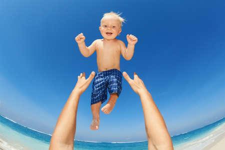 Vader handen gooien van de hoge lucht vrolijke baby jongen in op wit zand zee strand. Buitenshuis gezond kind activiteit, actieve levensstijl en plezier op familie zomervakantie met zoon op tropisch eiland