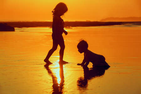 On sunset sea sand beach siblings - baby boy and little girl swimming with fun and playing with sun reflection in low tide pools. Water activity on family summer holidays with children on Bali island