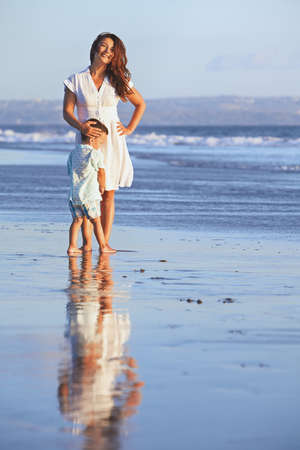 Idyllic portrait with reflection of happy smiling beautiful mother and baby boy on sea beach on background of sunset sky. Motherhood, family lifestyle and summer vacation with child on tropical resort Banco de Imagens